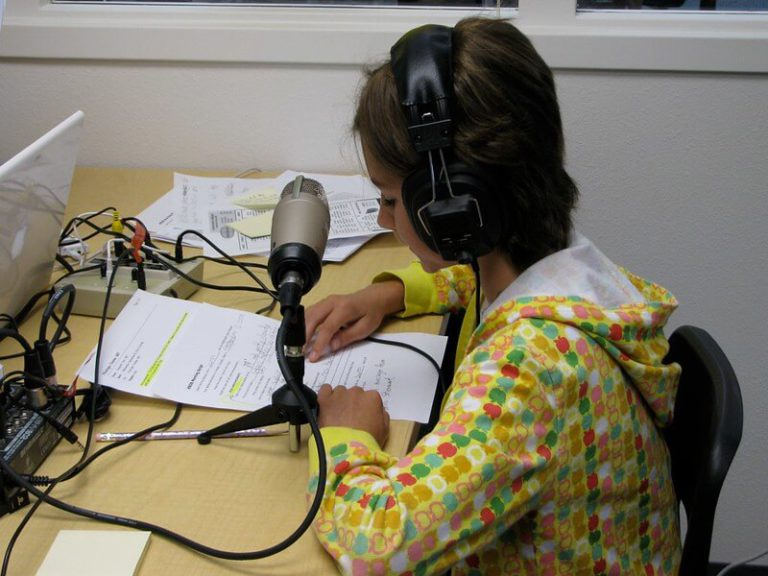 A student records her script into a microphone to be used as part of an educational podcast.