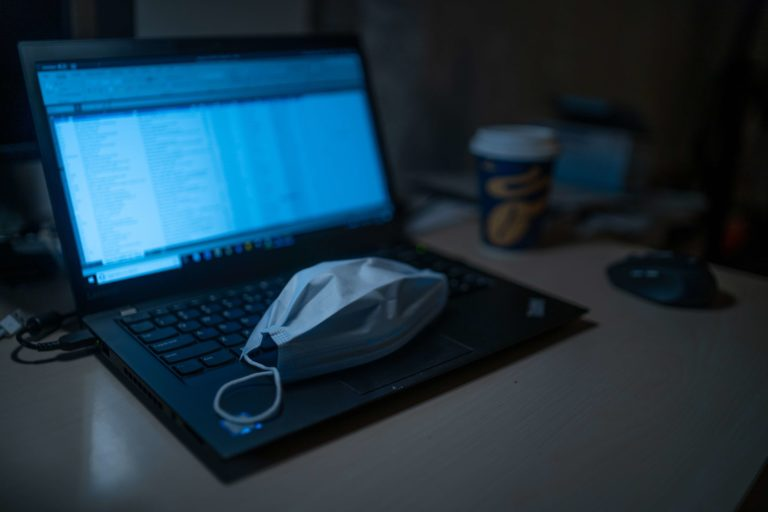 A COVID-19 mask is taken off as an employee is working from home on a laptop